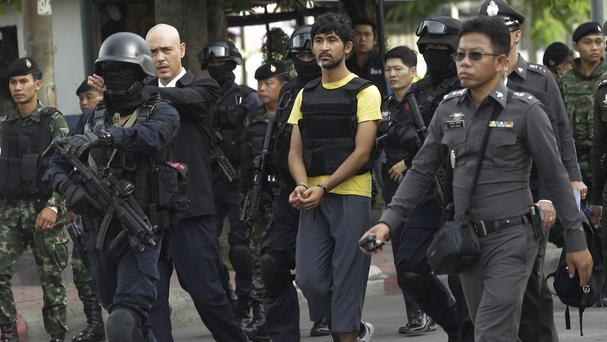 Police officers escort a key suspect in last month's Bangkok bombing, identified as Yusufu Mierili, outside Hua Lamphong railway station during a re-enactment of the August 17 bombing (AP)
