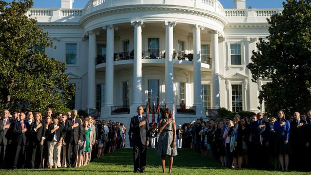 US president Barack Obama, first lady Michelle Obama and others pause on the South Lawn of the White House as a bugler plays