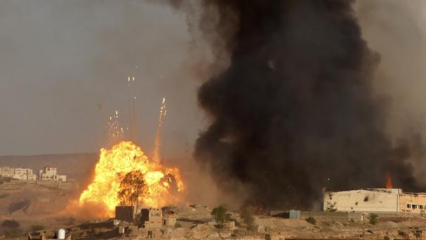 An explosion and smoke rise after an air strike by the Saudi-led coalition at a weapons depot in Sanaa. (AP)