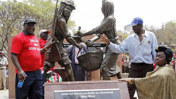 People gather near the sculpture of the Mau Mau war veterans at Uhuru park during the unveiling of the Mau Mau veteran memorial in Nairobi, Kenya (AP)