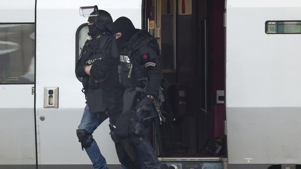 Anti-terror police carry a man who locked himself in a toilet of a Paris-bound train in Rotterdam central station (AP)