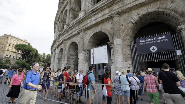 Tourists queue in front of the Colosseum as notices inform visitors of the temporary closure. (AP)
