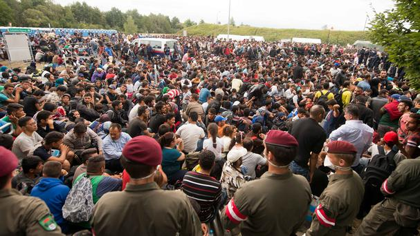 Migrants queue up for buses after they arrived at the border between Austria and Hungary near Heiligenkreuz, about 180km (110 miles) south of Vienna (AP)