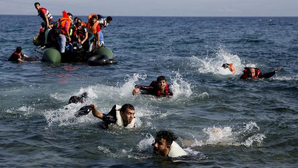 Migrants whose boat stalled at sea while crossing from Turkey to Greece swim to approach the shore of the island of Lesbos (AP)