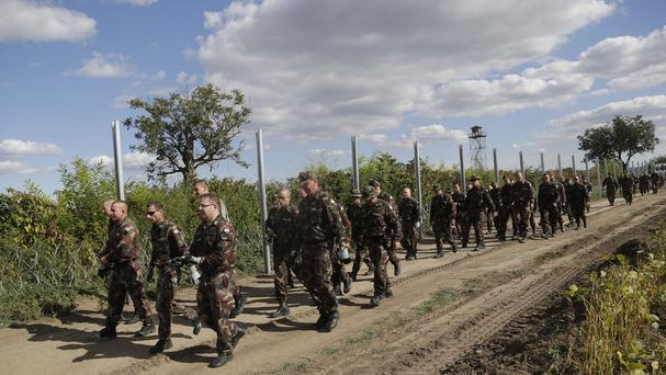 Hungarian soldiers walk past a razor wire fence that is being built along the border with Croatia near the village of Sarok. (AP)