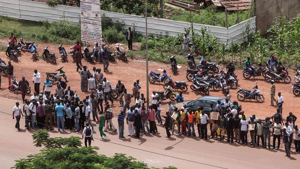 Anti-coup protesters stand near the hotel where talks took place in Ouagadougou. (AP)