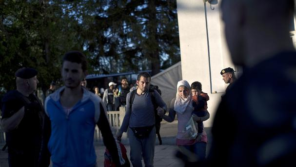 People walk past a police line as they board a train close to Croatia's border with Serbia. (AP)