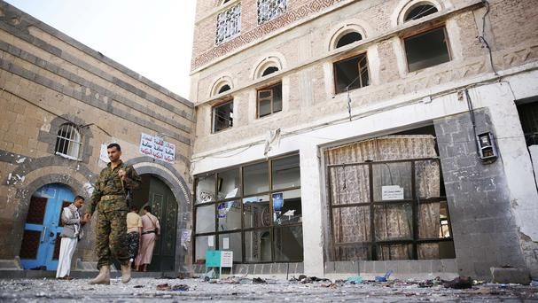 Shiite fighters, known as Houthis, inspect the scene at the al-Balili mosque in Sanaa, Yemen (AP)