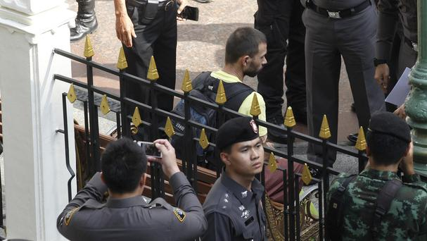 A key suspect in last month's Bangkok bombing, Adem Karadag, takes part in a re-enactment as Thai police say they are ready to prosecute him and Mieraili Yusufu (AP)