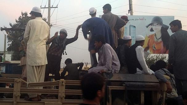 Taliban fighters and young men on an army truck on a street in Kunduz - the Afghan government says it has retaken control of the city (AP)