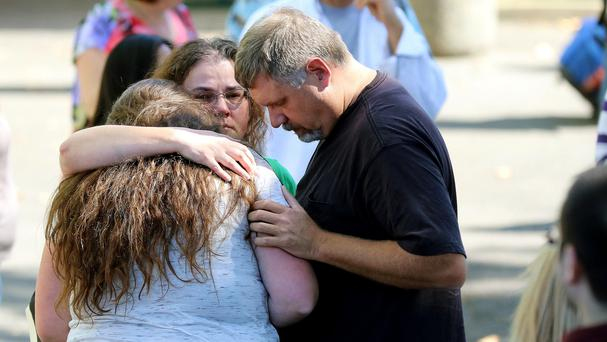 Friends and family are reunited with students at the local fairgrounds after a deadly shooting (AP)