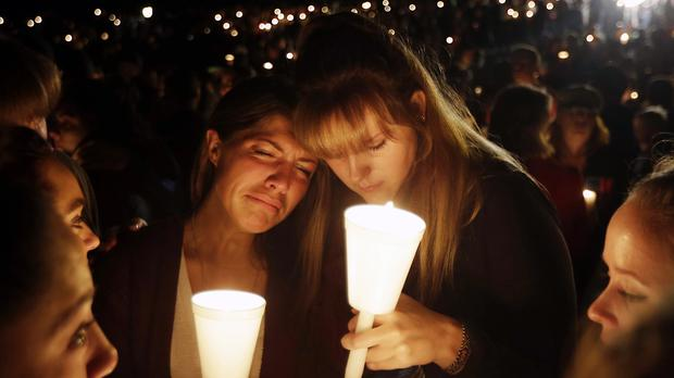 Kristen Sterner, left, and Carrissa Welding, students of Umpqua Community College, embrace each other during a vigil for those killed at the college (AP)