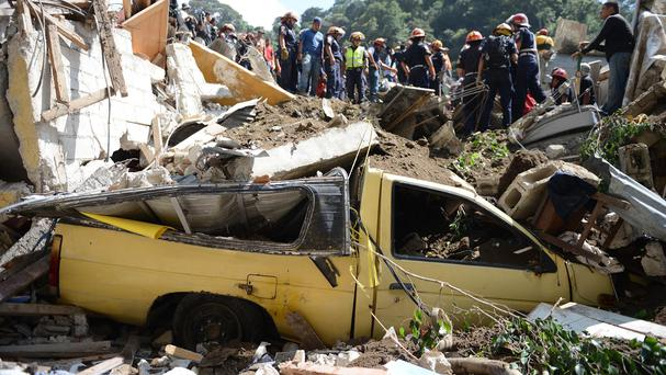 A vehicle sits crushed by debris caused by a mudslide in Cambray (AP)