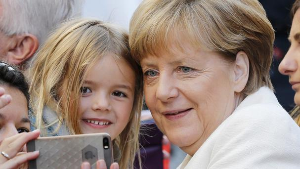 German Chancellor Angela Merkel poses for a selfie with five-year-old Marie during the celebrations to mark the 25th anniversary of the German reunification in Frankfurt (AP)