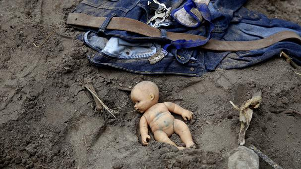 A doll and clothing lay in the mud as rescue workers continue to search the site of a mudslide in Cambray (AP)