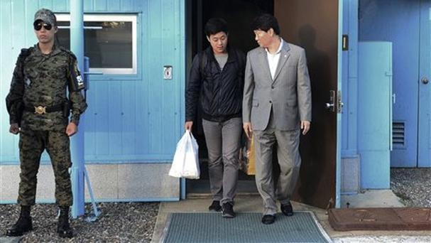 Won Moon Joo is escorted by a South Korean official at the border village of Panmunjom in Paju, South Korea (The South Korean Unification Ministry via AP)