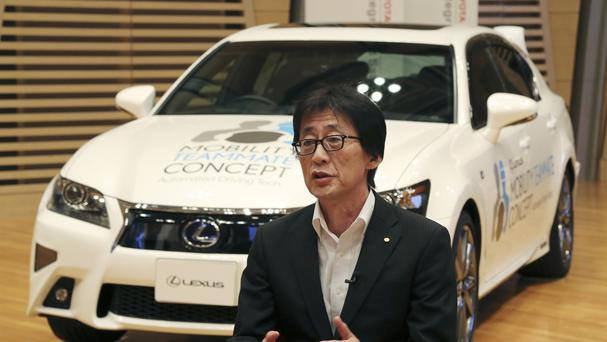 Chief Safety Technology Officer of Toyota Moritaka Yoshida in front of the automated driving test vehicle in Tokyo. (AP)
