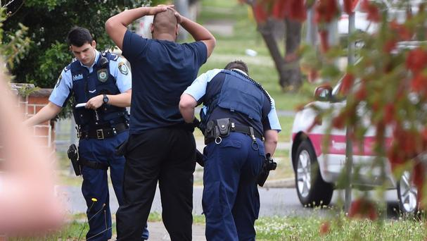 Police search a man and his vehicle near a house in Guildford, Sydney (AAP/AP)