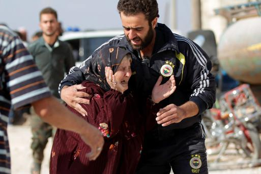 A man comforts a woman whose relatives were killed, at a site hit by what activists were airstrikes carried out by Russian air force in Maasran town, in the southern countryside of Idlib, Syria