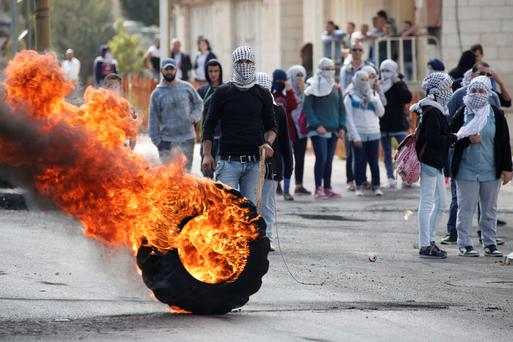 Palestinian stone throwers clash with Israeli security forces (unseen) in Beit El, near the West Bank city of Ramallah, on October 8, 2015.