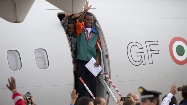 Eritrean refugees wave as they board an Italian Financial police aircraft which will take them to Sweden, at Rome's Ciampino airport (AP)