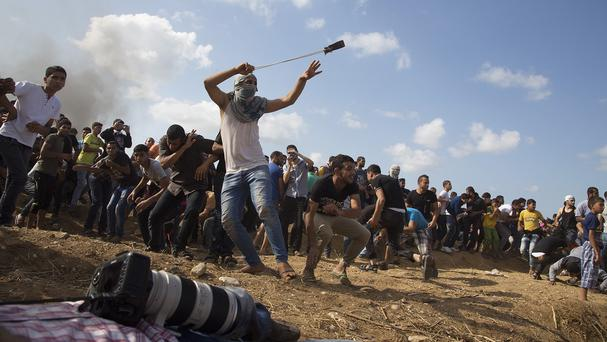 A Palestinian protester hurls stones at Israeli soldiers during clashes at the Israeli border. (AP)