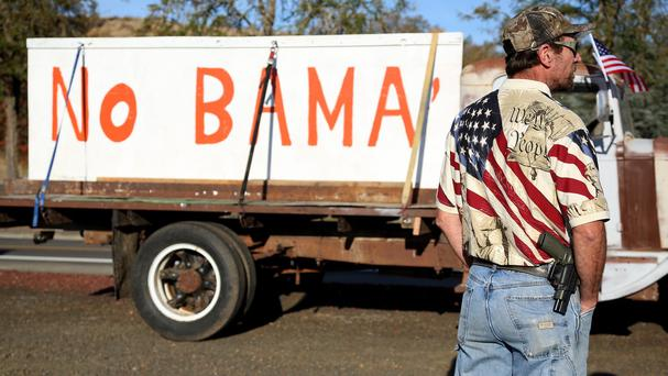Gun-toting protester Michael Johnson waits outside Roseburg Municipal Airport for Barack Obama's arrival to meet families of the college shooting victims (AP)