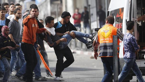 An injured Palestinian demonstrator is carried to an ambulance during clashes with Israeli troops in Hebron, West Bank (AP)