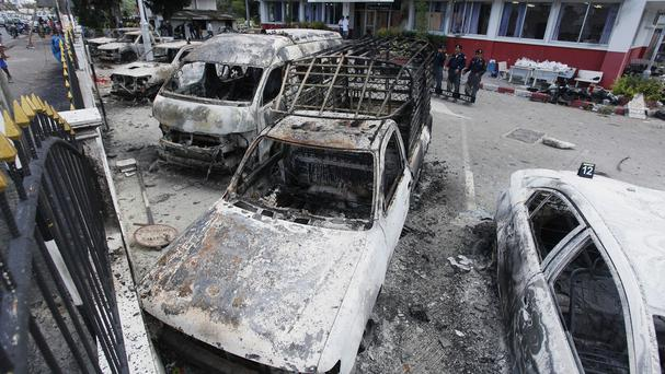 Thai policemen stand guard behind their burnt vehicles at a police station in Phuket (AP)