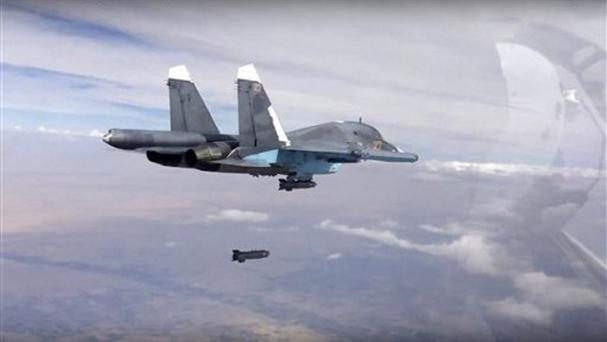A bomb is released from a Russian Su-34 strike fighter in Syria (Russian Defence Ministry Press Service via AP)