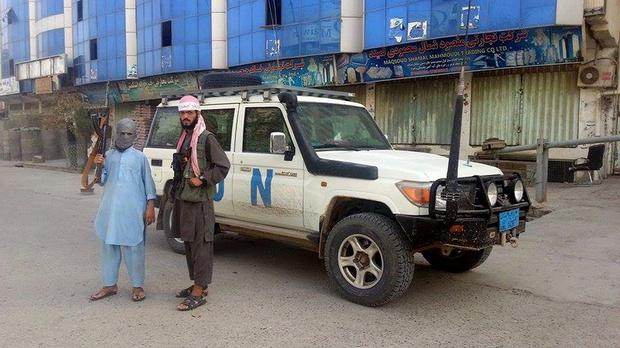 Taliban fighters pose for a photo next to a UN vehicle they plundered in Kunduz, Afghanistan. (AP)