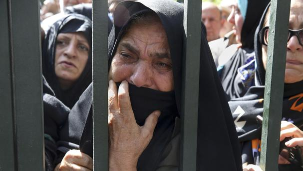 An Iranian mourner weeps during a funeral ceremony, attended by thousands of mourners, for some of the pilgrims who were killed in a stampede during the hajj pilgrimage in Saudi Arabia last month. (AP)