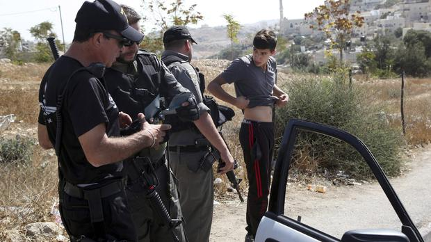 Israeli border police search a man driving out of the Palestinian neighbourhood of Jabal Mukaber in Jerusalem. (AP)