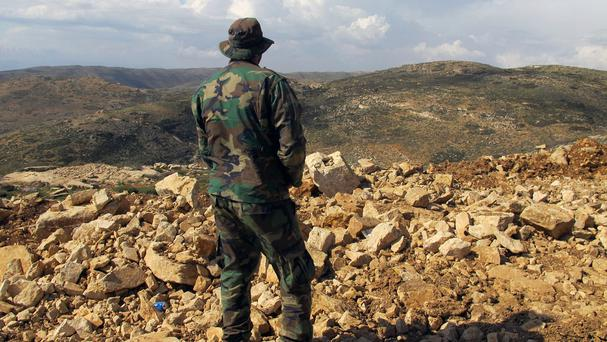A Hezbollah fighter looks towards Syria while standing in the fields of the Lebanese border village of Brital (AP)