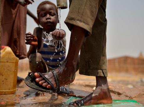 Children bathing at a contaminated borehole at Rier village, in south Sudan's Unity state, near an abandoned oil treatment facility which was once a crucial part of South Sudan's mainstay industry