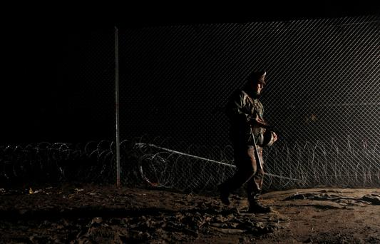 SHUT OFF: A Hungarian soldier walks past a fence put on the border with Croatia. Hungary's right-wing government declared its southern frontier with Croatia off limits to migrants, blocking entry with a metal fence and razor wire