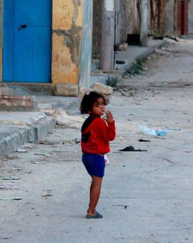 CIVIL LIFE: A girl walks along a deserted street in Tariq al-Bab neighbourhood of Aleppo