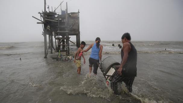 Residents carry their belongings towards their house on stilts as strong wind and rain caused by Typhoon Koppu hit the coastal town of Navotas, north of Manila, Philippines (AP)