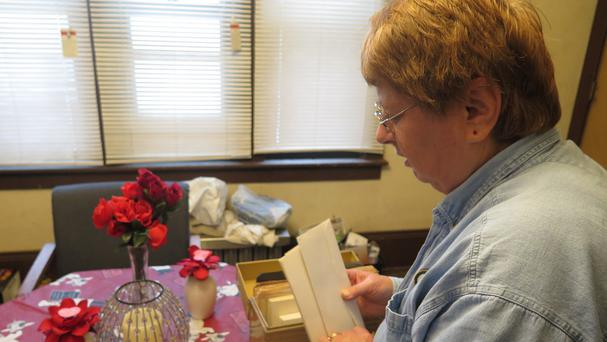 Carolyn Tousignant with clippings about the 1982 disappearance of her daughter Carrie Ann Jopek. (AP)