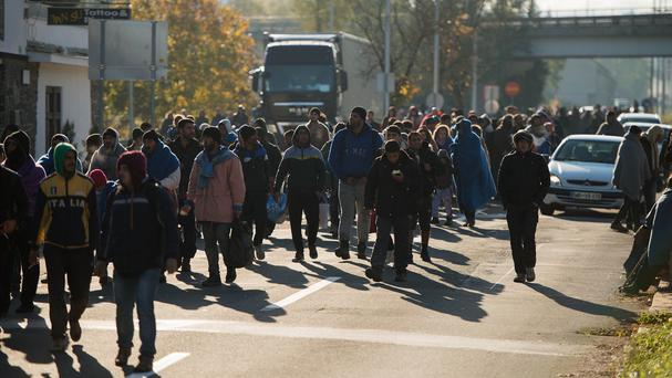 Migrants walk along a street to the Austrian-Slovenian border in Sentilj, Slovenia. (AP)