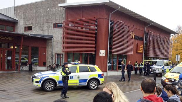 Emergency services attend the scene after a masked man attacked people with a sword at the Kronan school in Trollhattan, near Goteborg in western Sweden (Stig Hedstrm/TT via AP)