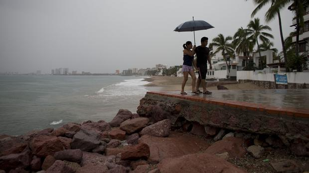 A couple walks along the waterfront under a steady rain as rainfall increases with the approach of Hurricane Patricia in Puerto Vallarta (AP)