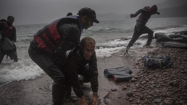 Migrants come ashore after travelling in a dinghy from the Turkish coast to the village of Skala Sikaminias on the Greek island of Lesbos (AP)