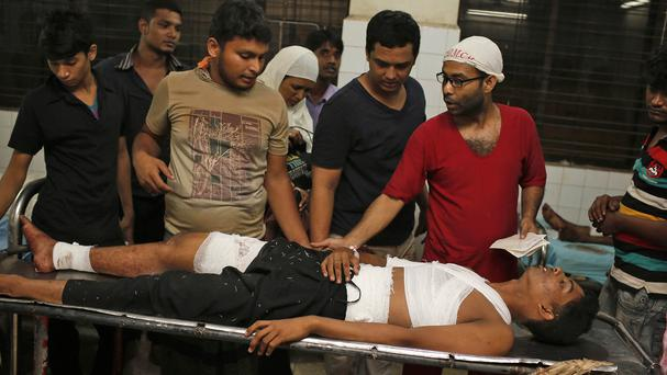 A Bangladeshi doctor, far right, attends to Ashikur Rahman, 22, after the bomb attack in Dhaka (AP)