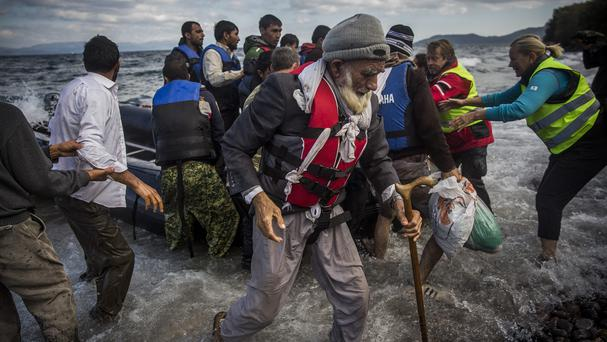 An elderly Afghan and other migrants arrive on the north-eastern Greek island of Lesbos after a journey by dinghy from the Turkish coast (AP)