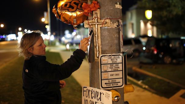 Teria Frank writes a message on a memorial in Stillwater, Oklahoma, near the site of the car crash (The Oklahoman/AP)