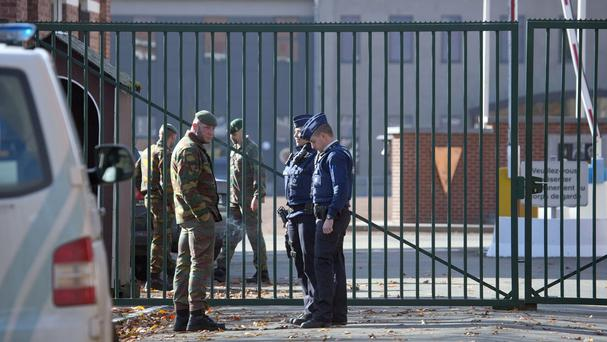 Police and military personnel stand outside a barracks in Belgium (AP)