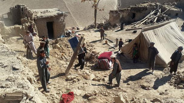 Afghan men carry their belongings after an earthquake in Takhar province (AP)
