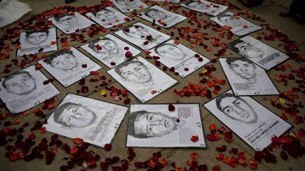 Drawings of missing rural college students are surrounded by flower petals during a protest over their disappearance (AP)