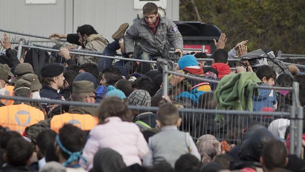 Migrants climb over a fence as they try to cross to Austria from Sentilj, Slovenia. (AP)